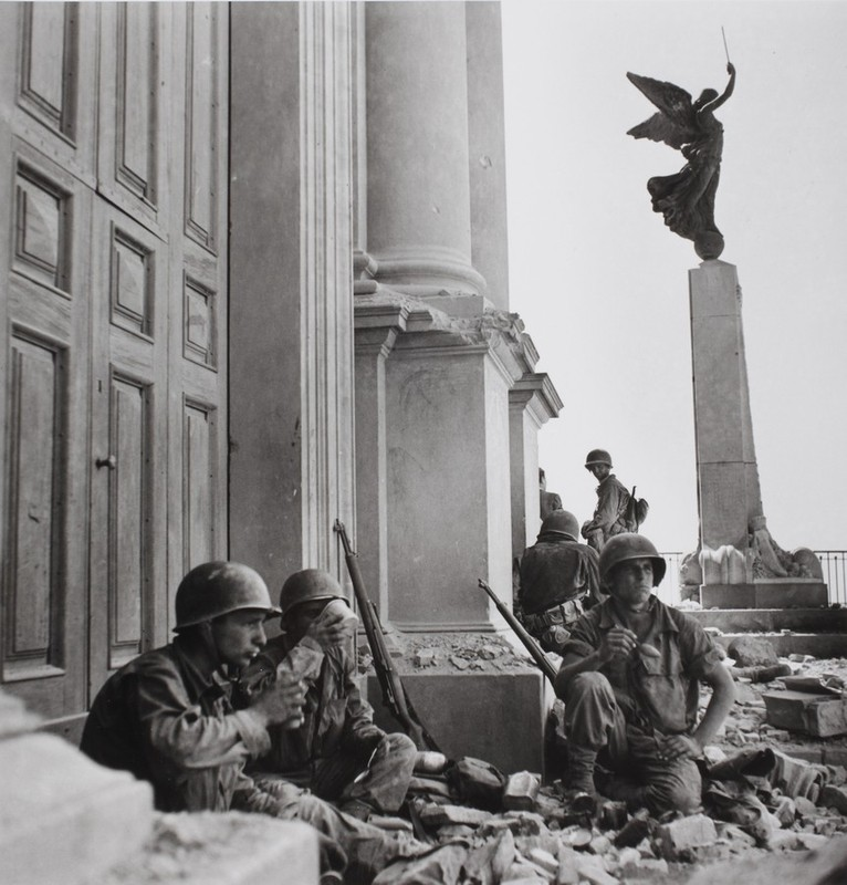 American soldiers near the entrance of the Maria SS Assunta Cathedral, Troina, after 6 August 1943. [Photograph by Robert Capa © International Center of Photography/Magnum - Collection of the Hungarian National Museum