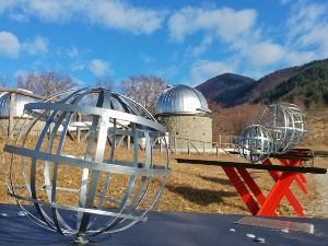 Some of the manufactured sculptures of the Stars Park representing the planets and, in the distance, the Pistoia Mountains Astronomical Observatory.
