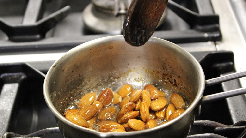 Mix the almonds with the sugar and cook over low heat, stirring constantly to avoid burning the almonds.
