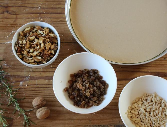 Top the castagnaccio mixture with rosemary needles, pine nuts, walnuts and a drizzle of oil
