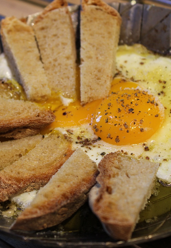 Serve the egg, still sizzling, directly in the frying pan, accompanied by slices of bread.